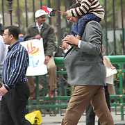 A father takes his excited son on his shoulders for a rally in Cairo's Tahrir Square on the Day of Justice and Cleansing.