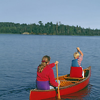 Lake of the Woods, Ontario, Canada. A mother and son canoe on Lake of the Woods.