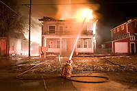 A firefighter works to put out a fire in Lincoln, Nebraska, February 2, 2007.