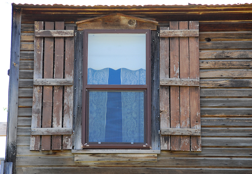 Window, shutters and curtains on a building in old mining town of Silver City, Idaho.