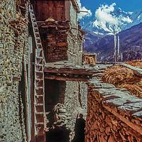 A trekker hikes through Manang Village, north of the Annapurna massif, Nepal
