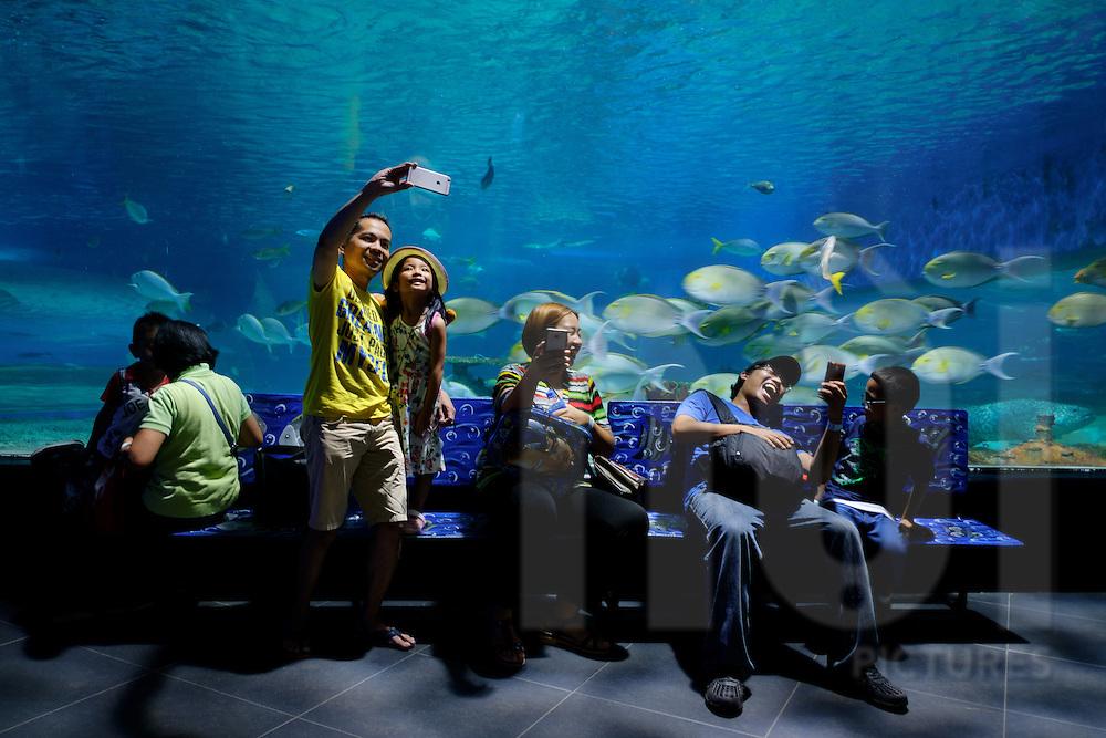 A filipino family enjoys their visit at Manila Ocean Park, Metro Manila, Philippines, Southeast Asia