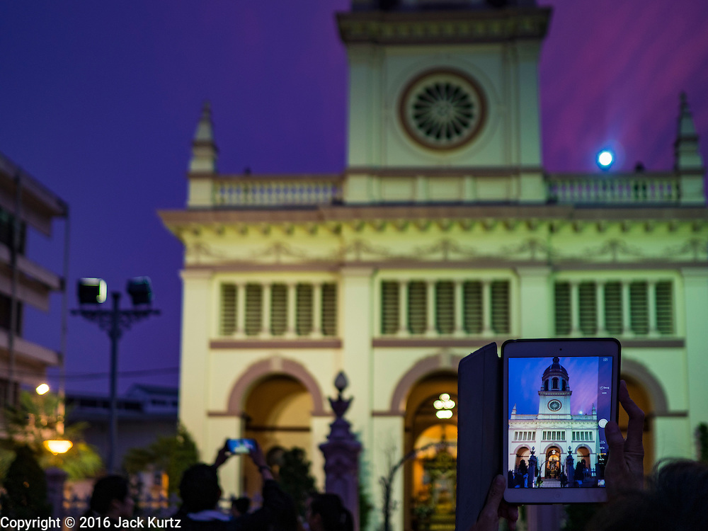 25 MARCH 2016 - BANGKOK, THAILAND: A person photographs the front of the church during Good Friday observances at Santa Cruz Church in Bangkok. Santa Cruz was one of the first Catholic churches established in Bangkok. It was built in the late 1700s by Portuguese soldiers allied with King Taksin the Great in his battles against the Burmese who invaded Thailand (then Siam). There are about 300,000 Catholics in Thailand, in 10 dioceses with 436 parishes. Good Friday marks the day Jesus Christ was crucified by the Romans and is one of the most important days in Catholicism and Christianity.      PHOTO BY JACK KURTZ