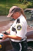 Policewoman age 35 writing ticket for illegal parking at Cedarfest Summer Music Festival.  Minneapolis Minnesota USA