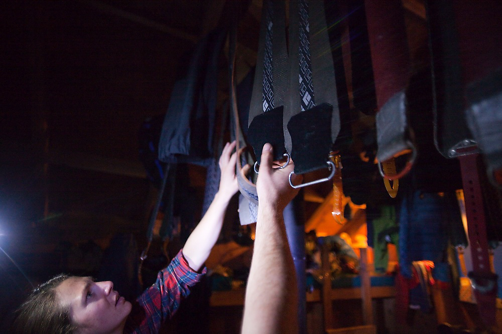 Meaghan Daly inspects the ski climbing skins drying hanging from the ceiling of the backcountry North Pole Hut, San Juan Mountains, Colorado.