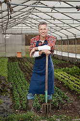 Man with pitchfork in greenhouse
