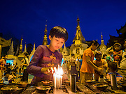 31 OCTOBER 2015 - YANGON, MYANMAR: Lighting candles and offering prayers as a form of merit making at Shwedagon Pagoda. Shwedagon Pagoda is officially known as Shwedagon Zedi Daw and is also called the Great Dagon Pagoda or the Golden Pagoda. It is a 99 metres (325 ft) tall pagoda and stupa located in Yangon, Burma. The pagoda lies to the west of on Singuttara Hill, and dominates the skyline of the city. It is the most sacred Buddhist pagoda in Myanmar and contains relics of four past Buddhas: the staff of Kakusandha, the water filter of Koṇāgamana, a piece of the robe of Kassapa and eight strands of hair from Gautama, the historical Buddha. The pagoda was built between the 6th and 10th centuries by the Mon people, who used to dominate the area around what is now Yangon (Rangoon). The pagoda has been renovated numerous times through the centuries. Millions of Burmese and tens of thousands of tourists visit the pagoda every year, which is the most visited site in Yangon.      PHOTO BY JACK KURTZ