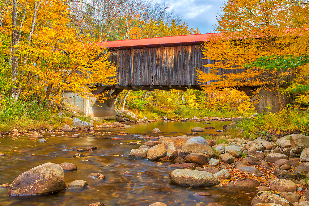 The iconic Durgin Covered Bridge framed by New England fall foliage. Durgin Covered Bridge spans the Cold River and is located in Sandwich, New Hampshire.<br /> <br /> New England fall foliage and Durgin Covered Bridge photography images are available as museum quality photography prints, canvas prints, acrylic prints or metal prints. Prints may be framed and matted to the individual liking and decorating needs:<br /> <br /> https://juergen-roth.pixels.com/featured/new-england-fall-foliage-framing-the-durgin-covered-bridge-juergen-roth.html<br /> <br /> All high resolution New Hampshire Covered Bridge photography images are available for photo image licensing at www.RothGalleries.com. Please contact me directly with any questions or request. <br /> <br /> Good light and happy photo making!<br /> <br /> My best,<br /> <br /> Juergen