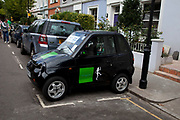 G-Wiz AEV (Automatic Electric Vehicle) parked sideways on Portobello Road, Notting Hill, West London. In the widow, advertising for health food store Planet Organic.