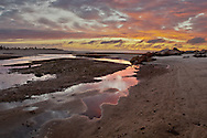 Dramatic sunset sky with low tide reflections at Paine's Creek in Brewster.