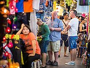 15 OCTOBER 2014 - BANGKOK, THAILAND:  Tourists shop in the Patpong Night Market, a popular tourist market in Bangkok. The number of tourists arriving in Thailand in July fell 10.9 per cent from a year earlier, according to data from the Department of Tourism. The drop in arrivals is being blamed on continued uncertainty about Thailand's political situation. The tourist sector accounts for about 10 per cent of the Thai economy and suffered its biggest drop in visitors in June - the first full month after the army took power on May 22. Arrivals for the year to date are down 10.7% over the same period last year.   PHOTO BY JACK KURTZ