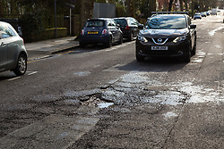 A SUV approaches a pothole on Brondesbury Road in leafy Queens Park, west London as the recent cold, wet weather has given rise to the increase in potholes and road surface deterioration in the capital. London, March 28 2018.