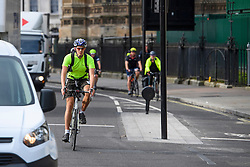 © London News Pictures. 25/08/2016. Cyclists ignore the cycle lane (right) and chose to join moving traffic while using a cycle lane on Abingdon Street, approaching Parliament Square. Cyclists repeatedly ignore new cycle lanes installed around westminster in central London. Between the hours of 8am and 9am on Wednesday 24/08/2016, 266 (two hundred and sixty six) cyclists passed through the red light at one of the newly installed  bike lanes and only 15 (fifteen) cyclists stopped.  The light system is designed to allow either vehicles or cyclists to pass at one time in order to make the junction safer for cyclists..... **VIDEO AVAILABLE** Photo credit: London News Pictures.