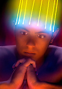 Praying young man with a glowing Tingler on his head.Black light