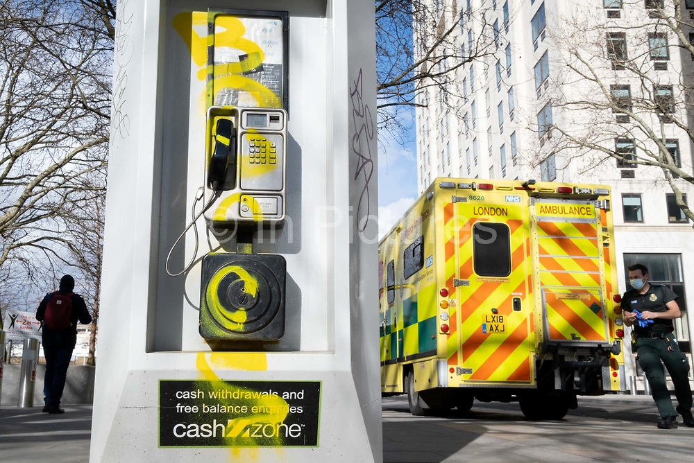 An NHS National Health Service paramedic prepares to attend an nearby emergency, at the rear of his ambulance, stopped alongside a public BT landline phone kiosk which has been vandalised by the spraying of yellow aerosol paint over its handset and keypad on the Southbank in Waterloo, on 11th March 2021, in London, England.