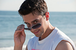 man at the beach lowering his sunglasses to reveal his eyes