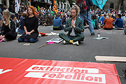 Extinction Rebellion meditation during disruption across 5 UK cities calling on Government to ACT NOW outside the Royal Courts of Justice after it was announced last week that more than 1,000 activists who participated in previous demonstrations were facing prosecution, on 15th July 2019 in London, England, United Kingdom. Extinction Rebellion is a climate change group started in 2018 and has gained a huge following of people committed to peaceful protests. These protests are highlighting that the government is not doing enough to avoid catastrophic climate change and to demand the government take radical action to save the planet.