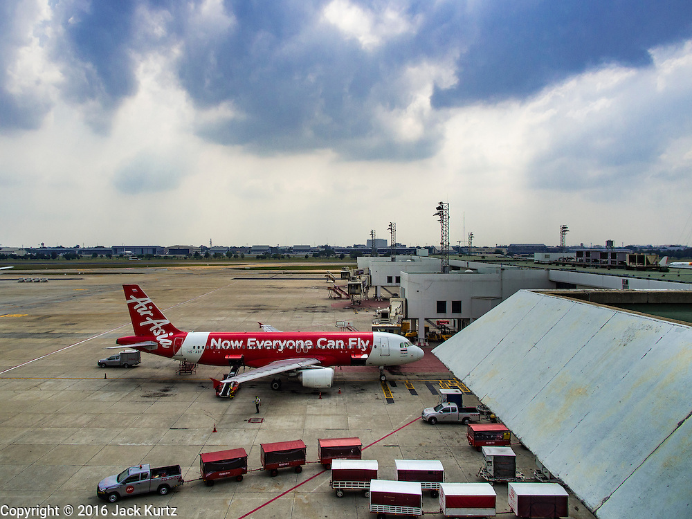 """23 FEBRUARY 2016 - BANGKOK, THAILAND:  An Air Asia Airbus aircraft on the tarmac at Don Mueang Airport. The Thai government has expressed an interest in Thai Airways, Thailand's flag carrier, acquiring a stake in Air Asia (Thailand). Executives from the two companies are expected to meet this week to discuss the proposal. The proposal comes at a time when the Thai aviation industry is facing more scrutiny for maintenance and training of air and ground crews, record keeping, and the condition of Suvarnabhumi Airport, which although less than 10 years old is already over capacity, and facing maintenance issues related to runways and taxiways, some of which have developed cracks. The United States' Federal Aviation Administration late last year downgraded Thailand to a """"category 2"""" rating, which means its civil aviation authority is deficient in one or more critical areas or that the country lacks laws and regulations needed to oversee airlines in line with international standards. Thai Airways, the flag carrier, has also faced a challenge with declining profits and alleged mismanagement. Air Asia is one of the most successful budget carriers in Asia.        PHOTO BY JACK KURTZ"""
