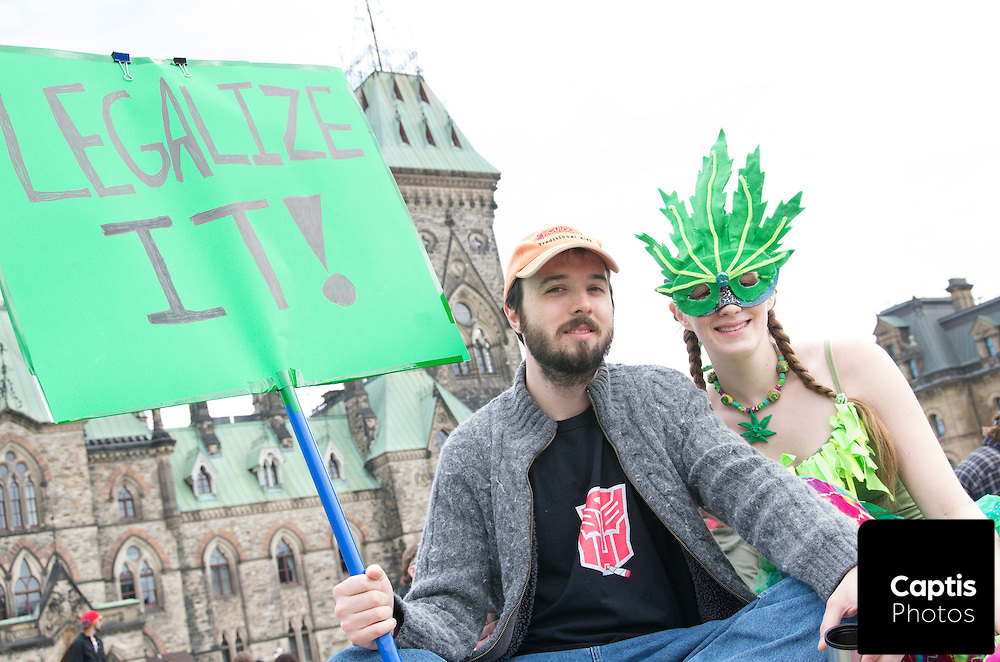 A couple holds a sign calling for legalization of cannabis. April 20, 2014.