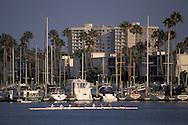 Rowing team crew boat skull through quiet blue water of Marina Del Rey, Los Angeles County, California