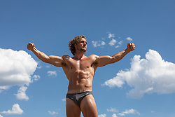 hot man in a speedo against the sky with his arms up