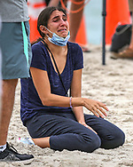 A woman reacts as she views the 12-story oceanfront condo tower partially collapsed early Thursday morning in the town of Surfside, spurring a massive search-and-rescue effort with dozens of rescue crews from across Miami-Dade and Broward counties on Thursday, June 24, 2021.