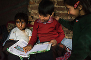 L-R: Azra, 5, Igra, 8, and Muzamil, 6, study in their temporary shelter in Narbal village, Jammu and Kashmir, India, on 24th March 2015. When the floods hit in the middle of the night, Shugufta and her family had to walk 5 miles to find shelter. Save the Children supported the family with shelter kits, blankets, hygiene items, food and tarpaulin, which they have used to build a temporary shelter next to their crumbled home. Photo by Suzanne Lee for Save the Children
