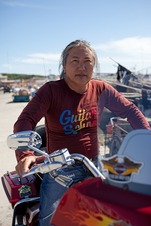 Portrait of the korean man sitting on his Harley Davidson motorbike in harbour / Jukbeon, South Korea, Republic of Korea, KOR, 05 October 2009.