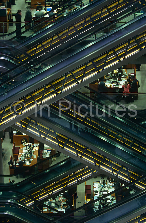 """From a high vantage point looking across the atrium of British architect Sir Richard Rogers' Lloyds building, we see the zig-zag-shape stripes of escalators, beyond which we see the desks of insurance underwriters at the Lloyd's building, home of the insurance institution Lloyd's of London which is located in Lime Street, in the heart of the City of London. Lloyd's is a British insurance market. It serves as a meeting place where multiple financial backers or """"members"""", whether individuals (traditionally known as """"Names"""") or corporations, come together to pool and spread risk. Unlike most of its competitors in the reinsurance market and is neither a company nor a corporation. The City of London has a resident population of under 10,000 but a daily working population of 311,000. The City of London is a geographically-small City within Greater London, England. The City as it is known, is the historic core of London from which, along with Westminster, the modern conurbation grew. The City's boundaries have remained constant since the Middle Ages but  it is now only a tiny part of Greater London. The City of London is a major financial centre, often referred to as just the City or as the Square Mile, as it is approximately one square mile (2.6 km) in area. looking across"""