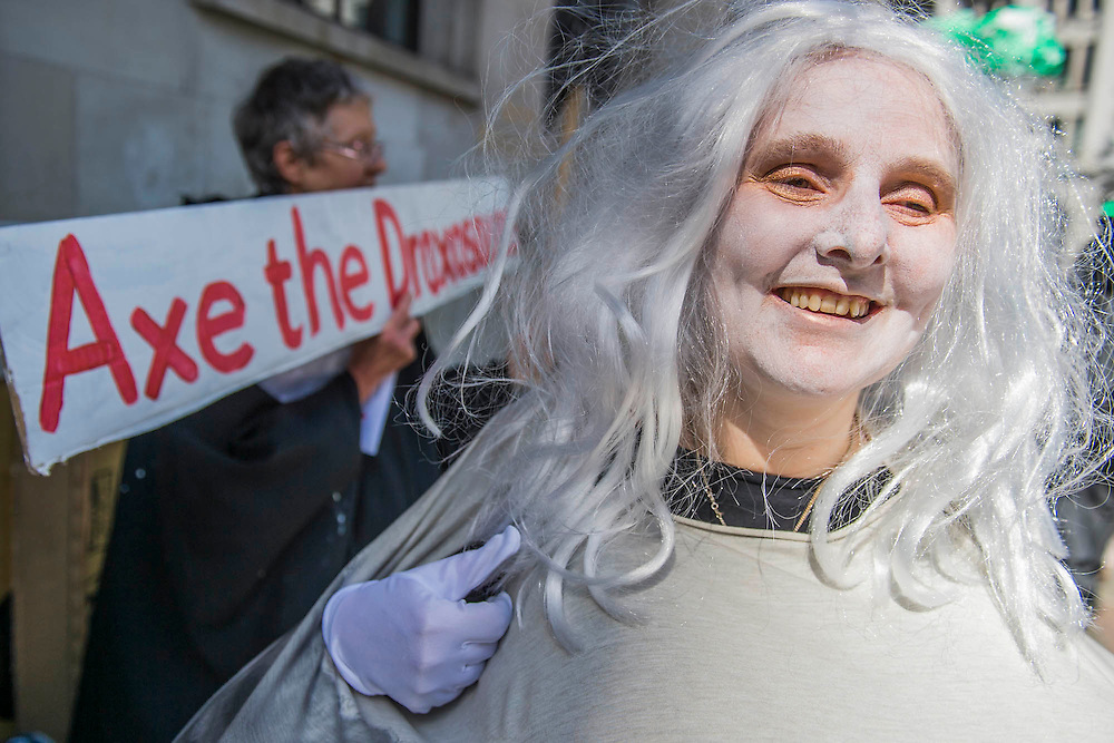 A woman dressed as a cooling tower adjust her smoke (hair) - #AxeDrax protest outside the annual Drax shareholder AGM. Protestors demanded cleaner, greener energy generation systems. They continued on to the Department of Energy and Climate Change to deliver a petition demanding that subsidies given to Drax, for burning biomass, be stopped for making climate change worse.