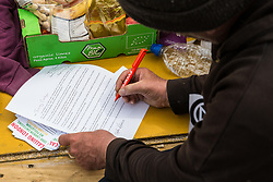 London, UK. 23rd April 2019. A climate change activist from Extinction Rebellion attending an assembly in Parliament Square writes a letter to his Member of Parliament, the Leader of the Opposition Jeremy Corbyn, requesting a meeting with him to discuss the issue of climate change. Activists later tried to deliver their letters to Parliament, but all but ten were prevented from doing so by the Metropolitan Police.
