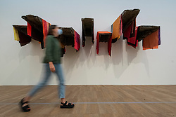 © Licensed to London News Pictures. 23/08/2021. LONDON, UK.  A staff member passes an untitled work at the preview of ARTIST ROOMS: Phyllida Barlow, a new exhibition of work by British artist Phyllida Barlow which includes several large-scale installations and a selection of drawings across her sixty-year career.  Photo credit: Stephen Chung/LNP