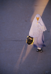 Africa, Morocco, Marrakesh, Muslim woman in robe walking through shaft of sunlight, viewed from above