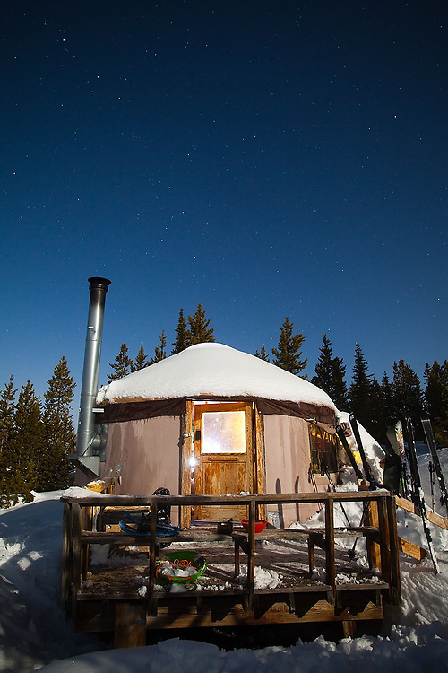 Skis at night outside the glowing Lower Montgomery Pass Yurt in Colorado State Forest State Park, Colorado.