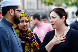 © Licensed to London News Pictures. 06/07/2015. London, UK. 7/7 survivor Gill Hicks talking to Imam Qari Asim outside King's Cross station on Monday, July 6, 2015 before walking to Tavistock Square with faith leaders to commemorate the 10th anniversary of 7/7 bombings by remembering those who lost their lives, as well as offering a message of peace and unity between people of different faiths and backgrounds. Photo credit: Tolga Akmen/LNP
