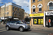 Expensive car drives past a pawn shop in Camberwell Green, London, UK. Sights like these emphasis the income gap between rich and poor in London and the UK, as people on low incomes struggle, wile others thrive.