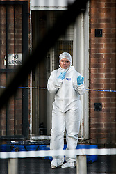 © Licensed to London News Pictures . 22/08/2016 . Manchester , UK . Crime scene outside 9a Atkinson Road , Urmston , Greater Manchester , where a man has been found dead and a woman was seen staggering through the street covered in blood , this afternoon (22nd August 2016) . Police tasered and then detained another man at the scene . Photo credit : Joel Goodman/LNP