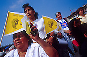 """jku032303052 - 31 JULY 2002 - MEXICO CITY, DF, MEXICO: People pray on the Zocalo in the historic center of Mexico City during a Papal mass televised to the Zocalo on large screen """"jumbotron"""" televisions. The mass, led by Pope John Paul II, was at the Basilica of Guadalupe in Mexico City, July 31, 2002. The Pontiff, making his fifth trip to Mexico, canonized Juan Diego, the Mexican Indian who first saw the image of the Virgin of Guadalupe in 1531. Juan Diego is now known at Saint Juan Diego. PHOTO © JACK KURTZ  RELIGION  INDIGENOUS  CULTURE  PATRIOTISM"""