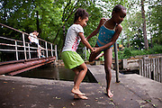 """BETHLEHEM, PA – MAY 27, 2011: Second generation Hispanics Nilda Lea Cruz, 7, and Niyanda Magagi, 9, play in the water at the Lehigh Canal on a Saturday afternoon at Sand Island in Bethlehem, Pennsylvania. Commonly known as """"The Box,"""" the water at Sand Island is one of several well known recreational spaces for the burgeoning Latino community in the town of Bethlehem.<br /> <br /> As the population of second and third generation Hispanics increases dramatically in the United States, a new boldness can be sensed among Latinos in America, stretching far beyond the southern border states. Demographers in Pennsylvania say the towns of Bethlehem, Allentown and Reading are set to become majority-minority cities, where Hispanics comprise a bigger portion of the population than whites. As this minority population increases dramatically in the region, Latinos are inching closer to their own realization of the American Dream, while gradually shifting the physical and cultural landscapes of their communities."""