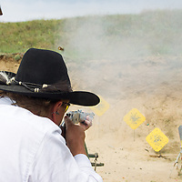 Participant rapid fires on targets with his weapon during the Cowboy Action Shooting European Championship in Dabas, Hungary on August 11, 2012. ATTILA VOLGYI