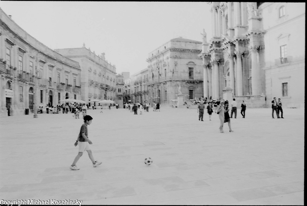 Kicking a ball in front of a greek temple. Piazza Duomo, Syracusa, Sicily.
