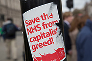 Sticker protesting against capitalist greed killing the NHS in London, England, United Kingdom.