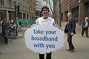 Smiling man holding advertising sandwich board for Cloud broadband internet, City of London, London, England