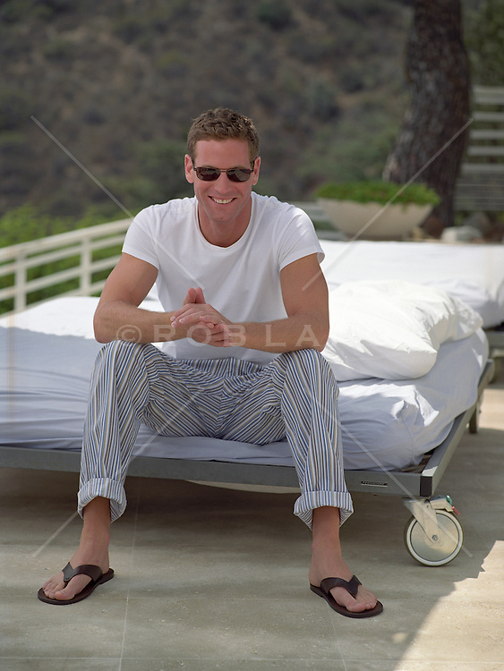 man in sunglasses sitting on the edge of an outdoor bed in Hollywood, CA