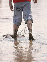 © Licensed to London News Pictures. 24/06/2012. Somerset, UK. A man walks barefoot through the mud. Festival goers enjoy the mud and the sunshine at The Sunrise Festival held at Bruton In Somerset today 24 June 2012. Photo credit : Jason Bryant/LNP