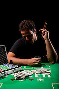 A young male gambler at the gambling table holding a cigar model release available