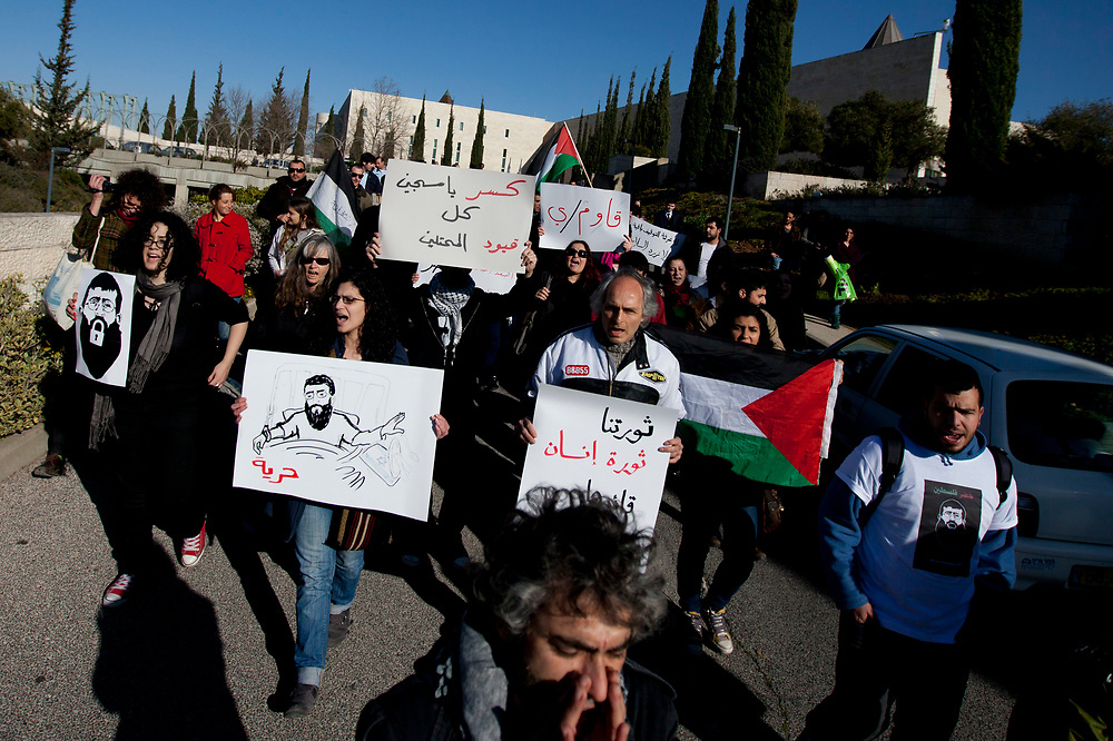 Palestinian and Israeli protesters and left-wing activists hold placards depicting Islamic Jihad leader Khader Adnan, who is jailed in Israel, during a demonstration in solidarity with Adnan, in front of Israel's Supreme Court in Jerusalem, on February 21, 2012. Adnan agreed to end his 66-day hunger strike over his imprisonment without charge, after reaching a deal with Israeli authorities that will free him in April.
