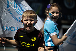 © Licensed to London News Pictures . 12/05/2019. Manchestr , UK . KRISTIAN MANDIC (seven) and LANA MANDIC (nine) from Stockport . Manchester City supporters watch the club's Premier League match at Brighton on a big screen in City Square at the Etihad Stadium. If Manchester City win the match they will win the title for the second time in a row . Photo credit : Joel Goodman/LNP