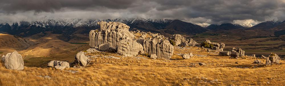 Flock Hill limestone boulders, autumn snowfall on Foggy Peak range, near Porter's pass and Castle Hill, Canterbury, New Zealand.