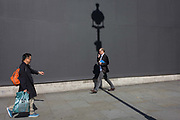 BBC Arts reporter Will Gumperts with a lamp post shadow against a grey construction hoarding in central London's Trafalgar Square. He walks through the dark diagonal line left by an ubnseen vertical lamp post. Gompertz was previously director of Tate Media, and appeared in a show at the Edinburgh Fringe in 2009 called Double Art History. Gompertz has written extensively for The Guardian and The Times newspapers. He is the author of What Are You Looking At?: 150 Years of Modern Art in the Blink of an Eye